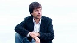 Der Jazz-Pianist Jan Lundgren sitzt auf einem Felsen am Meer.  Foto: Thomas Schloemann