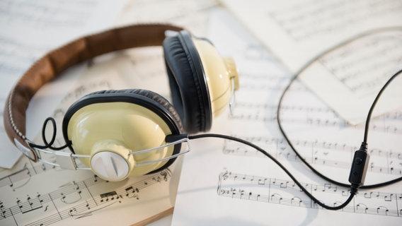 Un auricular se encuentra en varios lados de la partitura.  © picture alliance - Bildagentur-online - Tetra Images