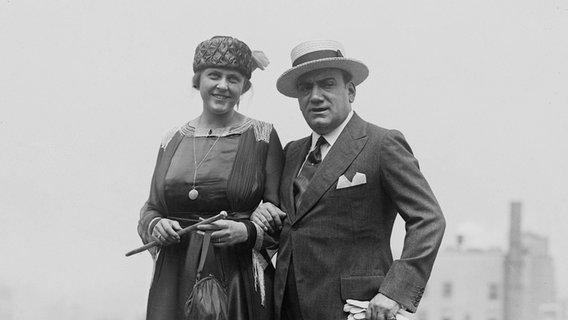 Penyanyi opera Italia Enrico Caruso berpose dalam foto hitam putih bersama istrinya, Dorothy Park Benjamin.  © Courtesy Everett Collectionx