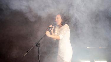 Schauspielerin Solène Garnier singt im Nebel in ein Mikrophon. Fotograf: Stephan Walzl