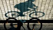Ein Fahrradfahrer der einen Schatten auf das Kopfsteinpflaster wirft. © jock+scott / photocase.de Foto: jock+scott