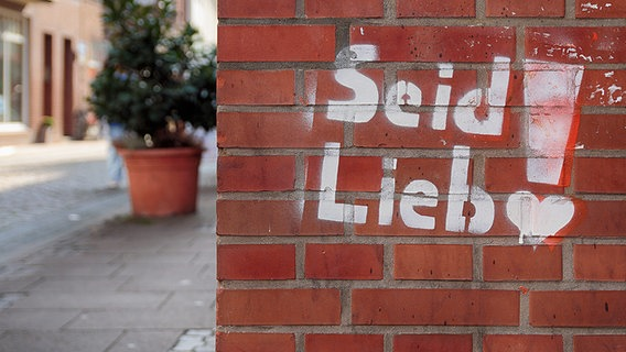 """Worte """"Seid Lieb"""" an eine Hauswand gesprüht. © photocase.de Foto: anune"""