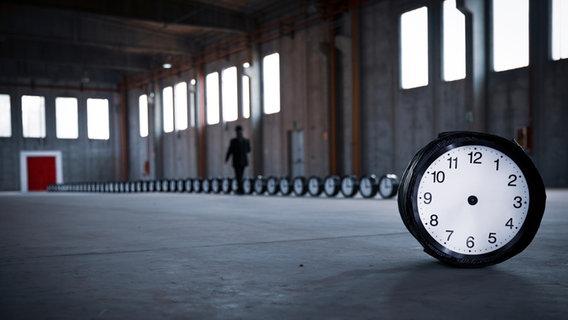 Una fila di orologi si trova in un edificio industriale vuoto.  Un orologio può essere visto dalla parte anteriore.  © Roberto Agagliate / photocase.de Foto: Roberto Agagliate
