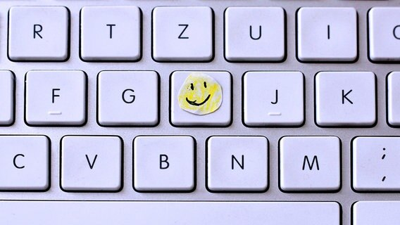 Ein kleiner gezeichneter Smiley klebt auf einer Tastatur. © photocase.de Fotograf: a_sto