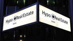 An einer Bankfiliale der Hypo Real Estate in Berlin leuchtet das Eingangsschild des Unternehmens. © dpa / picture-alliance