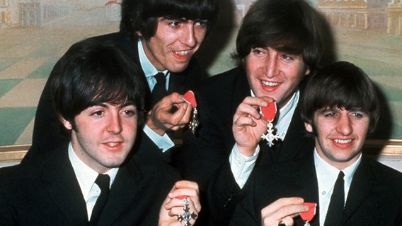"Paul McCartney, George Harrison, John Lennon und Ringo Starr mit den Orden ""Member of the Order of the British Empire"" (Aufnahme vom 26. Oktober 1965) © dpa"