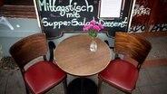 Zwei Stühle und ein Tisch in einem Lokal. © picture alliance Foto: Christian Charisius