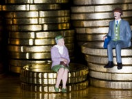 Eine Plastik-Frauenfigur sitzt auf einem kleinen Euro-Münzen-Stapel, eine Männerfigur auf einem größeren. © picture-alliance/dpa Fotograf: Lehtikuva Tuomas Marttila