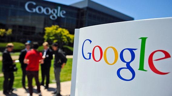 Auf dem Gelände des Google-Sitzes in Mountain View im US-Bundesstaat Kalifornien stehen mehrere Mitarbeiter zusammen. Im Vordergrund ist das Google-Logo zu sehen. © dpa picture alliance Fotograf: Ole Spata