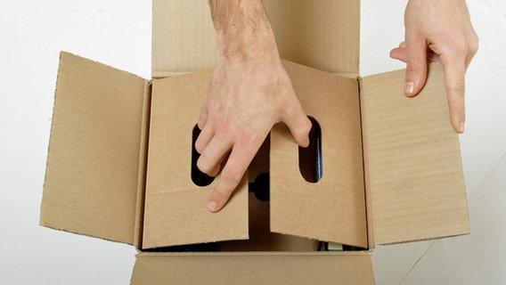 Hände bauen einen Karton zusammen © picture-alliance Fotograf: Michael Memminger / CHROMORANGE