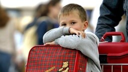 Kind sitzt auf einem Kofferwagen © dpa