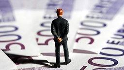 Figur betrachtet Geldscheine © picture-alliance/chromorange