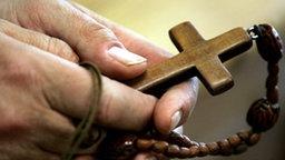 Hände halten ein Holzkreuz © picture-alliance/ dpa/dpaweb Fotograf: picture-alliance