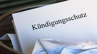 """Papier mit der Aufschrift """"Kündigungsschutz"""" in einem Mülleimer © Picture-Alliance / dpa"""
