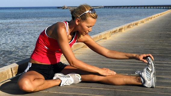 Eine Frau macht Dehnübungen am Strand © picture-alliance/ dpa/dpaweb