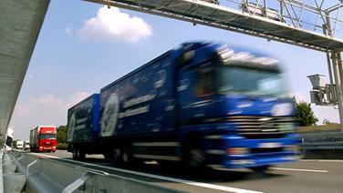 Ein Lastwagen fährt auf einer Autobahn unter einer Maut-Kontrollbrücke durch. © dpa Foto: Rolf Vennenbernd