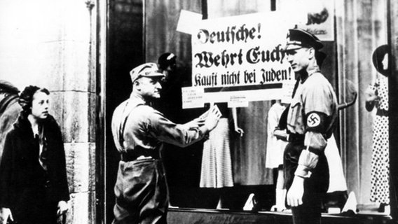 SA men are sticking a poster that reads' Germans!  Defend yourselves!  Don't buy from Jews on the window of a Jewish shop.  © picture-alliance / dpa Photo: dpa