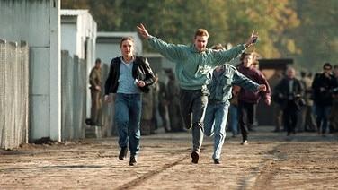Jubelnd laufen drei junge Ost-Berliner am 10. November 1989 durch einen Berliner Grenzübergang. © dpa