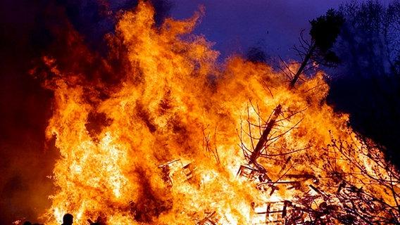 Loderndes Feuer, davor Menschen als Scherenschnitt erkennbar. © dpa Fotograf: Carsten Rehder
