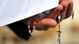 Hand eines Priesters mit Rosenkranz © dpa Fotograf: Jochen Lübke
