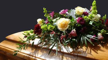 Ein Blumengesteck auf einem Holzsarg © Mary Stark / fotolia Foto: Mary Stark