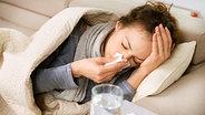 Kranke Frau liegt auf einem Sofa und schnäuzt sich die Nase © Fotolia Foto: Subbotina Anna