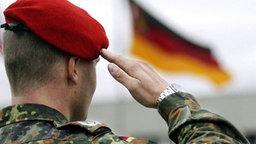 Soldat salutiert vor deutscher Fahne © picture-alliance / dpa