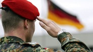Soldat salutiert vor deutscher Fahne © picture-alliance / dpa