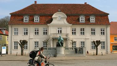 Das Fritz-Reuter-Literaturmuseum mit dem Denkmal in doppelter Lebensgröße davor (1911, Wilhelm Wandschneider) in Stavenhagen (Kreis Demmin). | picture-alliance