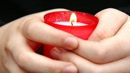 Hände halten ein brennendes Grablicht. © picture-alliance / ZB Fotograf: Patrick Pleul