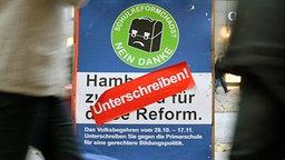 Eine Helferin sammelt Unterschriften für ein Volksbegehren der Gegner der Hamburger Schulreform. © dpa Foto: Angelika Warmuth