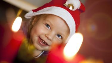 Ein kleines Kind mit Weihnachtsmütze sitzt vor einem Adventkranz mit brennenden Kerzen. © picture alliance / EXPA /APA/ picturedesk.com Fotograf: EXPA