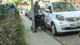 Eine Frau versucht mit ihrem Rollator an einer Laterne vorbei zu schieben.
