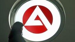 Eine Frau vor einem Fenster mit dem Logo der Agentur für Arbeit © dpa-Bildfunk Foto: Franz-Peter Tschauner