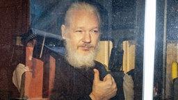 Wikileaks-Gründer Julian Assange sitzt in einem Polizeiauto und schaut aus dem Seitenfenster. © dpa picture alliance/ZUMA Press Foto: Rob Pinney