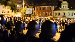 Polizeibeamte stehen in Bautzen auf dem Kornmarkt Versammlungsteilnehmern aus dem politisch rechten Spektrum gegenüber. © dpa