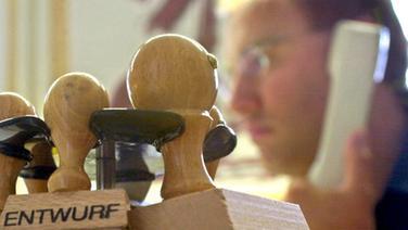 Ein Beamter sitzt hinter einem Halter mit Stempeln und telefoniert © dpa