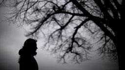 Eine Frau steht neben einem kahlen Baum © dpa Foto: Julian Stratenschulte