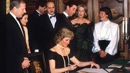 Prinzessin Diana trägt sich am 8. November 1987 im Beisein von Bürgermeister Klaus von Dohnanyi (links) ins Goldene Buch der Stadt Hamburg ein. © dpa