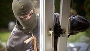 Maskierter Einbrecher bricht ein Fenster auf. © Fotolia.com Fotograf: bilderbox