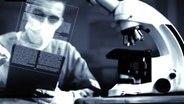 Ein Mann sitzt vor einem Mikroskop. © Screenshot