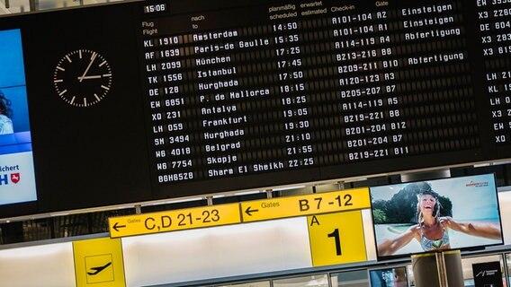 Auf einer Anzeigetafel am Flughafen werden die geplanten Abflüge aufgelistet. © NDR Foto: Julius Matuschik
