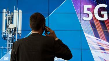 """Ein Mann steht vor einem Plakat mit dem dem Schriftzug """"5G"""". © picture alliance/dpa Foto: Boris Roessler"""