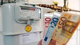 Geldscheine vor einem Gaszähler © dpa Foto: Armin Weigel