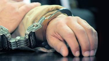 Mit Handschellen fixierte Arme © dpa Fotograf: Ronald Wittek