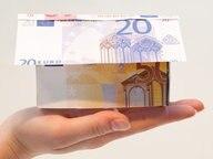 Ein Haus aus Geld auf einer Hand. © picture alliance / dpa Themendienst Fotograf: Franziska Koark