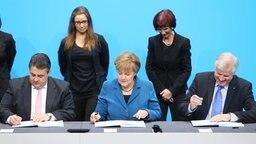 Sigmar Gabriel, Angela Merkel und Horst Seehofer unterzeichnen den Vertrag zur Großen Koalition. © dpa-Bildfunk Foto: Hannibal Hanschke