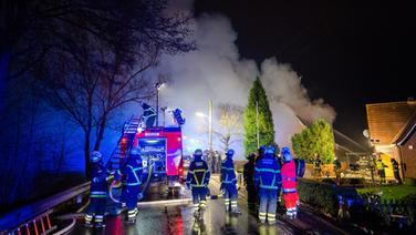 Feuerwehrleute löschen einen Hausbrand in Hamburg-Altengamme © dpa Fotograf: Daniel Bockwoldt