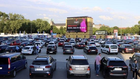 """Auf einer LED-Leinwand im Autokino auf dem Heiligengeistfeld steht """"Willkommen! Schön, dass ihr da seid!"""", davor parken Autos. © picture alliance/Geisler-Fotopress Foto: gbrci/Geisler-Fotopress"""