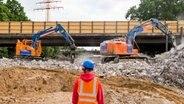 Mehrere Bagger reißen wird die Brücke der B5 Bergedorfer Straße über die Autobahn A1 bei Hamburg-Billstedt ein. Ein Bauarbeiter betrachtet das Geschehen. © picture alliance / dpa Foto: Daniel Bockwoldt